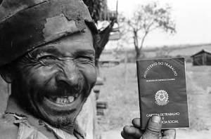 Homem exibe carteira de  trabalho assinada aoós muitos anos desempregado