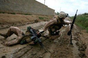 Soldados do Iraque se escondem logo após seu amigo ser atingido em um confronto na cidade de Bagdá