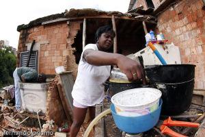 Moradora da favela da perdida mostra situação de moradia após fortes chuvas de junho na Bahia: imagem desoladora