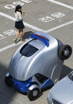 A woman walks past folded Armadillo-T, a foldable electric vehicle, at the Korea Advanced Institute of Science and Technology (KAIST) in Daejeon
