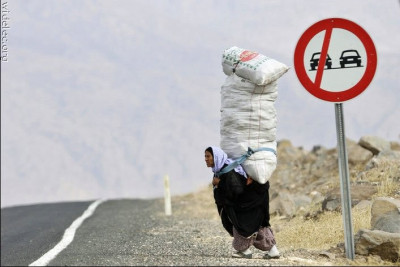 mulher carregando sacos nas costas