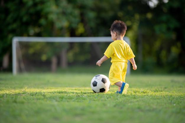 criancas-jogando-futebol-no-campo-verde_62292-15